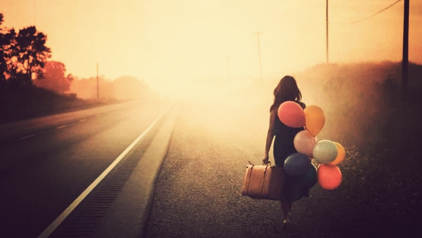 woman-walking-along-the-road-with-suitcase-and-balloons